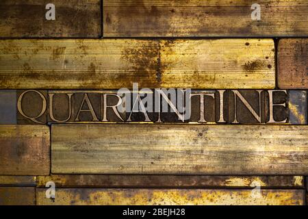 Photo of real authentic typeset letters forming Quarantine text on vintage textured grunge copper background