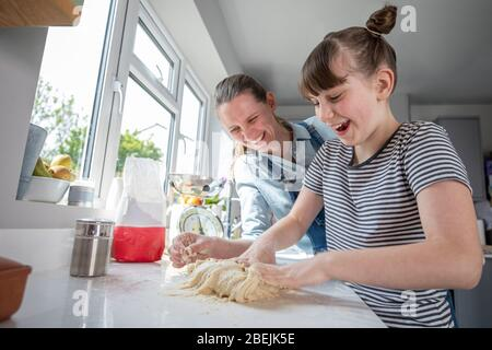 Mother And Daughter Having Fun In Kitchen At Making Dough For Home Baked Bread Together