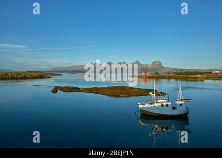 A lone fishing boat moored in the still summer seascape of South Heroy and Alsta and the Seven Sisters mountain range in Helgeland Nordland Norway