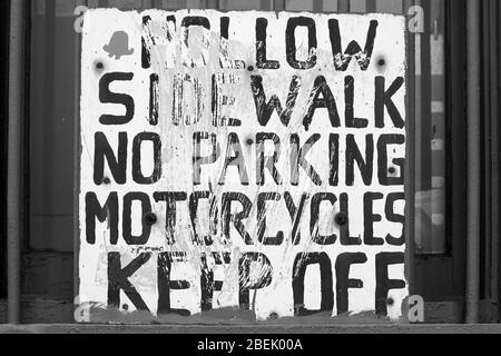 Hollow sidewalk. No parking. Motorcycles keep off. Hand painted prohibition sign on a window in Manhattan, New York City, United States of America. - Stock Photo