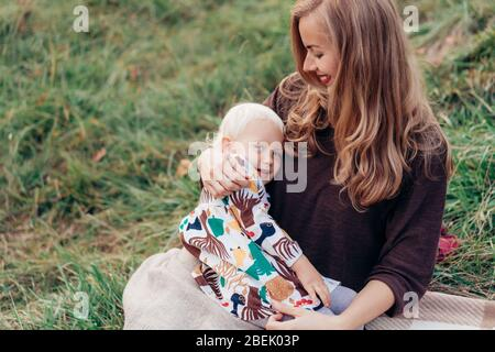 Cute mom hugs and toddler daughters. Family lifestyle in nature.