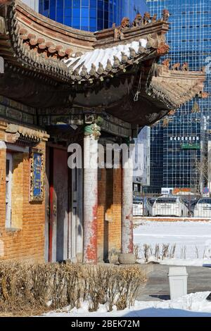 ULAANBAATAR, MONGOLIA, March 9, 2020 : Traditional monastery in the city center contrasts with huge modern buildings. - Stock Photo