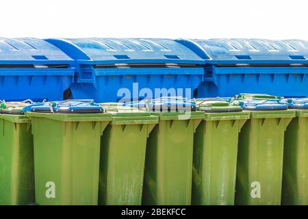 Large blue and small green waste containers isolated on a white background - Stock Photo