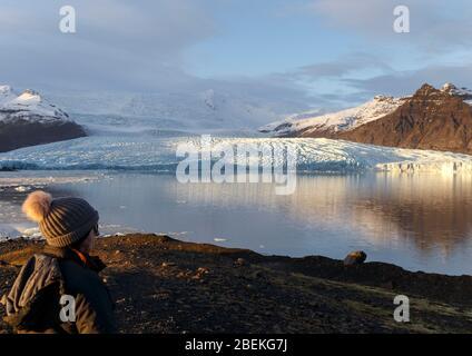 Person beside Fjallsarlon iceberg lagoon, beneath Fjallsjokull glacier. Vatnajokull National Park, Sudhurland, Iceland