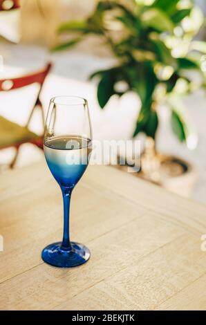 Glass of blue color with champagne table in cafe - Stock Photo