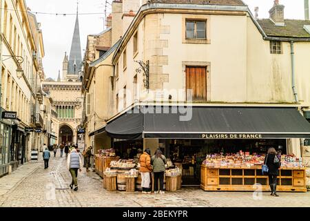 Rue Musette in Dijon's medieval old town, with customers browsing outside a gourmet grocery shop. Dijon, France. February 2020. - Stock Photo