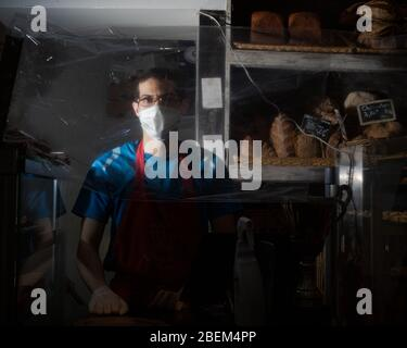 Jules, an employee at Tout Autour du Pain in the 3rd Arrondissement, poses during his shift behind the counter protected by plastic wrap, in Paris, France on April 12th, 2020. As a staple of French culture, many bakeries have remained open in Paris during the Covid-19 lock down. As such, bakers and employees have been thrown onto the front lines of the pandemic, often wearing face masks and working behind counters protected by plastic wrap or plexiglass to continue serving the people and maintain a semblance of normality. (Photo by Daniel Brown/Sipa USA) - Stock Photo