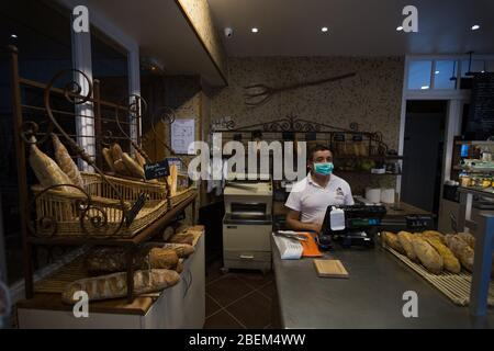 Alexandre, the owner of L'Atelier D'Antan in the 14th Arrondissement, poses while working behind the counter in Paris, France on April 10, 2020. 'It's important to stay open to feed people,' he said. 'It's like during the second World War: you have to stay open for the people to eat bread. Bread is the first necessity. I have to stay open for my people.' As a staple of French culture, many bakeries have remained open in Paris during the Covid-19 lock down. As such, bakers and employees have been thrown onto the front lines of the pandemic, often wearing face masks and working behind counters p - Stock Photo