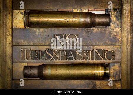 Photo of real authentic typeset letters forming No Tresspassing text bordered by 50 caliber gun cartridges on vintage textured grunge copper backgroun