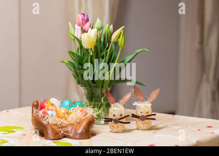 Easter holiday with colored eggs and flowers. colorful tulips near the painted Easter eggs of different colors - Stock Photo