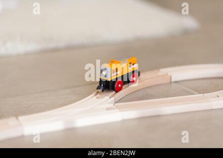 Wooden toy train on a track with blurred background - Stock Photo