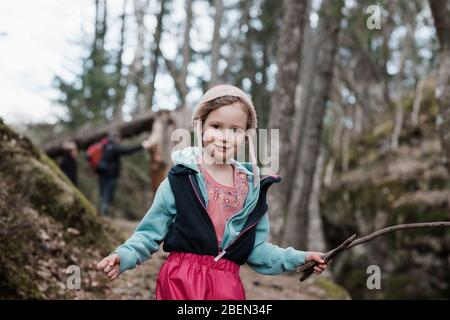portrait of a young girl holding a stick whilst hiking in Sweden