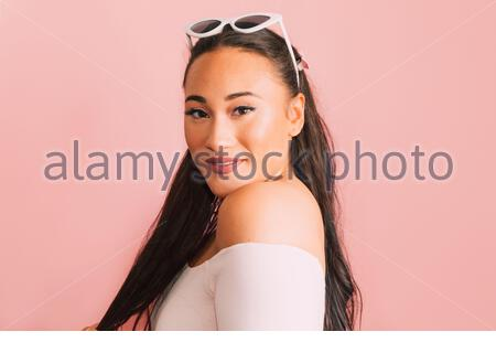 Portrait of Multiracial Female Posing in front of Pink Wall - Stock Photo