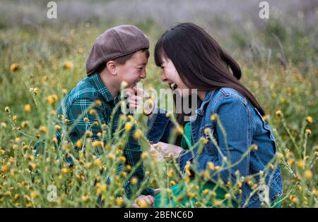 Pregnant Asian mother with long black hair wearing a green dress and blue denim jacket her son in a brown newsboy cap laughing together in a meadow - Stock Photo