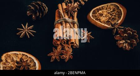 Background of dry slices of orange, cinnamon and star anise, ingredients for preparation mulled wine on black background Stock Photo