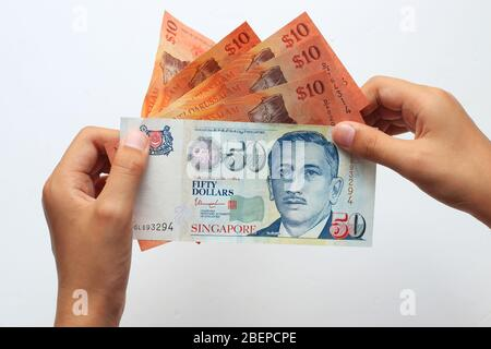Hand holding Singaporean $50 and Brunei $10 currencies isolated against white background - Stock Photo