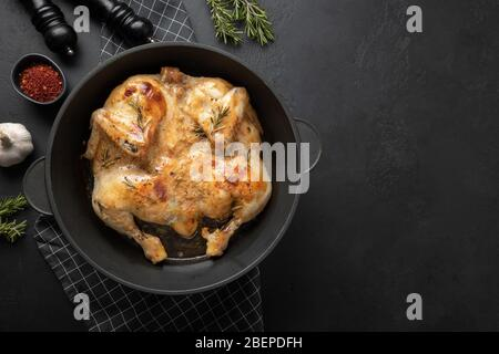 Roasted chicken with spices in cast iron pan on black table. Space for text or recipe. - Stock Photo