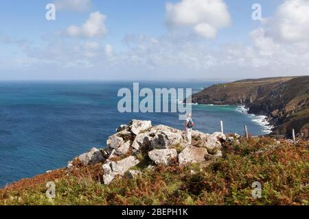 Woman standing on a rocky clifftop looking at the stunning coastal scenery near St Ives in Cornwall, England, UK - Stock Photo
