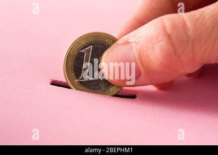 Hand putting one euro coin into a moneybox on pink background