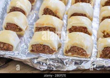 Uncooked British style sausage rolls on foil - traditional mince meat pastry wrapped snacks