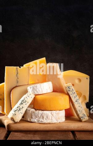 Cheese variety, many different types of cheeses, a side view on a black background with a place for text - Stock Photo
