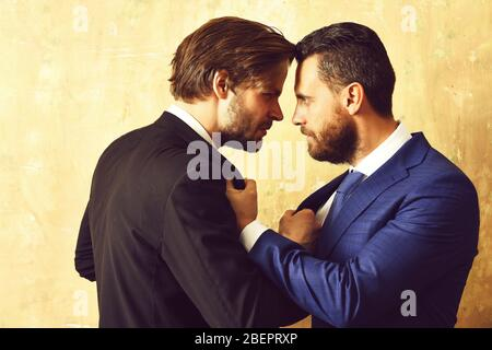 Business conflict or rivalry. Partners in suits holding each other with angry faces in office - Stock Photo