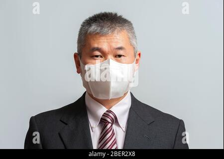 Front view of middle aged Asian man with suit and tie wearing white disposable 3D face mask for protection against novel coronavirus (COVID-19).