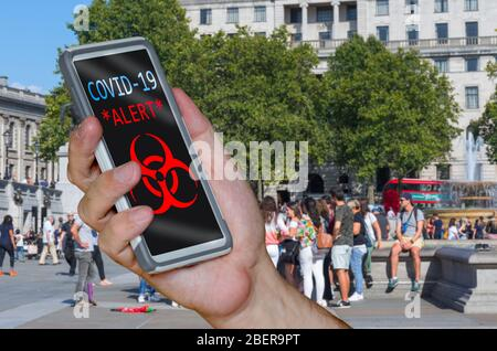 Depiction of Coronavirus COVID19 NHS contact tracing / detection app on a smartphone, used in a busy city to indicate nearby people who are infected. - Stock Photo
