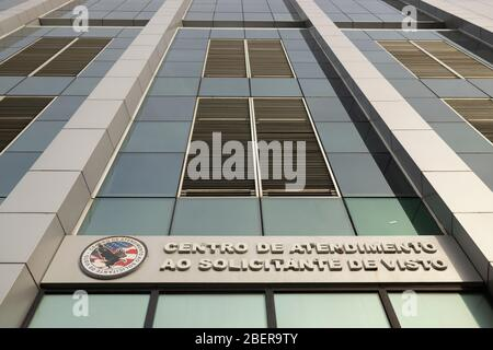 Look up at modern contemporary architecture of the visa request center with reflection of the sky and United States emblem. TRANSLATION: 'VISA REQUEST - Stock Photo