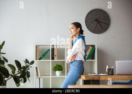 Image of young asian secretary woman thinking and standing by table while working in office