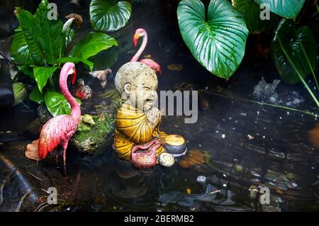 Statue of little Buddhist monk in the tropical garden with pink flamingo in Wat Saket Golden Mountain Temple in Bangkok - Stock Photo