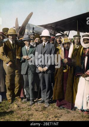 First Viscount Herbert Samuel, Colonel T.E. Lawrence, and Sheik Amir Abdullah in front of a biplane. - Stock Photo