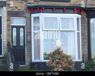 Display of cut coloured paper forming the symbol of a rainbow and sunshine as message of hope during the Coronavirus crisis in bay window of UK house