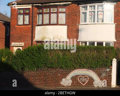 A chalked rainbow and message of support and gratitude to the NHS on the front wall of a house in Sheffield UK also with rainbows in upstairs window.