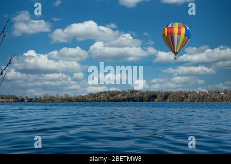 a colourful hot air balloon flies over the blue water of a lake - Stock Photo
