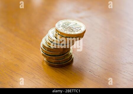New One Pound Coins in a stack on a table - Stock Photo