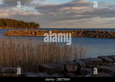Breakwater in spring seaside sunshine in Espoo with no people - Stock Photo