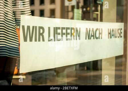 Shop window of a shop with a sign saying 'We deliver home', in German, with displays and the reflection of the surroundings in blur at the time of the - Stock Photo