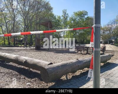 Empty , abandoned children playground or play field in park or forest with slide closed with police barrier warning tape due to corona virus covid-19