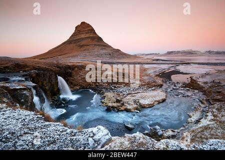 Kirkjufellsfoss, Iceland - Nov 27, 2019: Long exposure during sunset over the Kirkjufellsfoss Waterfall with Kirkjufell Mountain in the background in Stock Photo