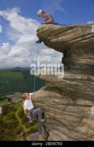 two friends are climbing at Stanage edge  in the Peak District - Stock Photo
