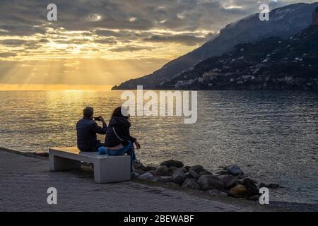 A couple enjoying a scenic sunset at Maiori waterfront on the Amalfi Coast, Campania, Italy