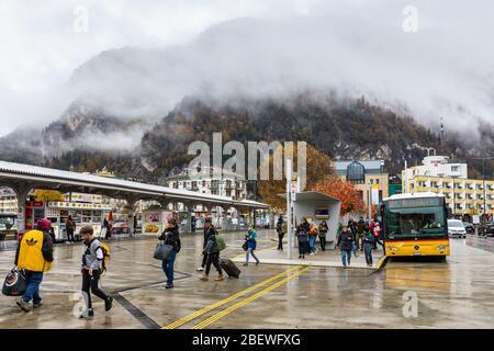 Interlaken, Switzerland - November 8, 2019: Passengers with baggage walking from Interlaken West Bahnhof public bus station on rainy day with foggy mo - Stock Photo