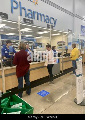SPRINGFIELD, MO, USA-April 15, 2020 Shoppers at a Walmart Pharmacy during the coronavirus COVID-19 pandemic.  Shields in front of employees and social distancing markers on the floor. - Stock Photo