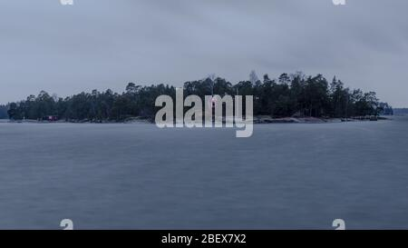 Isolated island in middle of stormy sea - Stock Photo