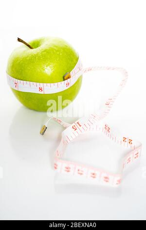 A whole green granny smith apple with a measuring tape wrapped around it to symbolize healthy eating & diet against a plain white background - Stock Photo