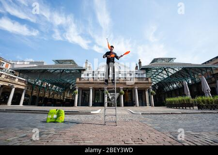 Nick Malinowski speaking Shakespeare and juggling whilst on a ladder to an empty Covent Garden, London. His act is recorded for World Buskers United a 24hr stream of buskers on the 25th April as the UK continues in lockdown to help curb the spread of the coronavirus. - Stock Photo
