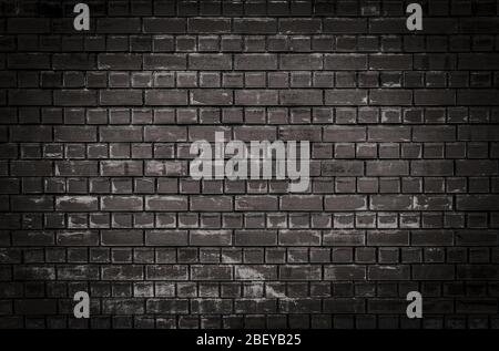 Texture or background of a dark brick wall with scratches and scuffs at night