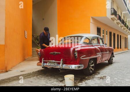 Person polishing his vintage Chevrolet Belair classic car, Havana old town, Cuba