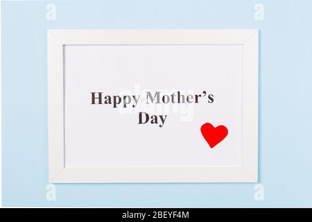 White picture frame with text Happy Mother's Day and red heart on light blue background . Happy Mother's Day concept. - Stock Photo